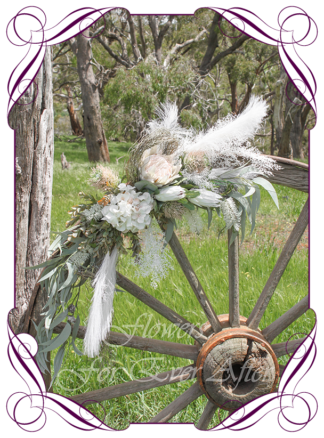 A Gorgeous Silk Artificial Australian native arbor arch wedding table decoration featuring faux flower hydrangea, ivory protea, dusty pink banksia, australian natives, pampas, and textures, gum leaves eucalypt, in a romantic elegant and unusual bridal style, rustic boho wedding decoration set. Made in Melbourne by Australia's Best Artificial Bridal Florist. Worldwide Shipping available