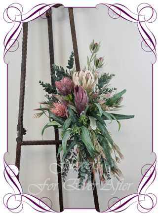 Realistic silk artificial fake flower rustic native Australian blush pink protea, mauve purple banksia gum leaves cascading arbor corner arch decoration wedding decor. Made in Melbourne. Shipping world wide. Buy online