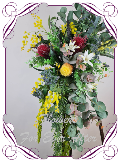 Silk artificial native Australian corner arbor arch backdrop floral decoration. Red, yellow, navy, orange, native Australian gum leaves foliage with banksia and wattle.Made in Melbourne Australia. Buy online, post worldwide.