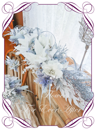 Blue White Silver Artificial floral Christmas Garland Centrepiece for table décor or mantel, featuring artificial white poinsettias, silk florals, glitter branches and artificial foliage's. Made by Melbourne's Best Silk Bridal Florist creating unique artificial wedding flower packages. Delivery worldwide. Custom orders welcome.